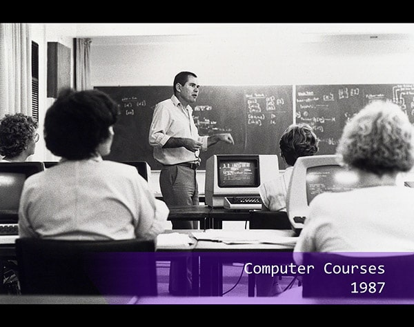 a teacher lecturing a class about computers in 1987
