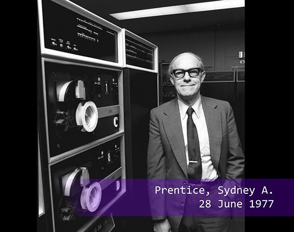 Sydney A Prentice poses next to a computer in 1977