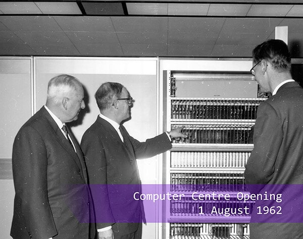 Three men looking at the computer at the Computer Centre opening in 1962