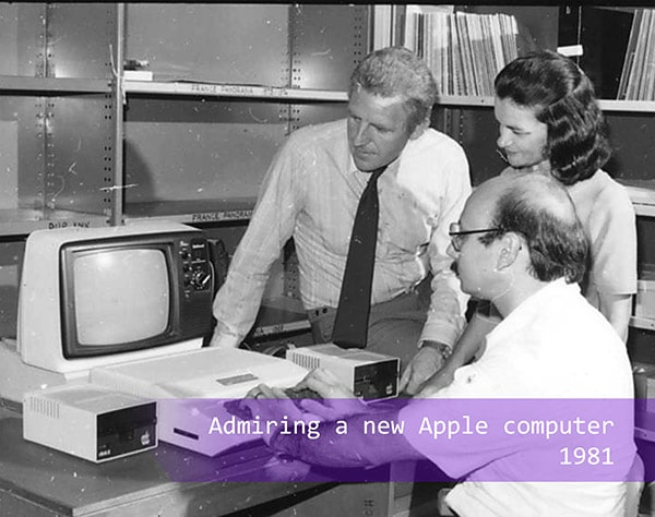 staff admiring a new Apple computer in 1981